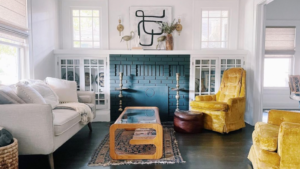 A living room with painted fireplace and styled accent furniture.